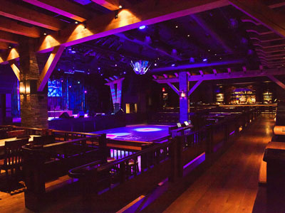 Inside the Ranch Saloon showing a wooden dance floor, stage, guitar disco ball, seating and bar
