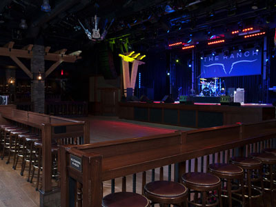 2 rows of stools around a dance floor, looking at a stage set with band equipment