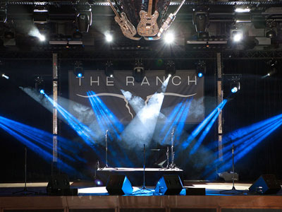 The stage with blue and white lights, microphones, sound equipment, and guitar disco ball