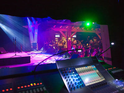 A sound booth looking at a stage with a crowded dance floor below