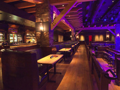 A row of booth seating located between a bar and a dance floor surrounded by wooden stools