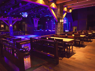 A row of wooden tables and chairs overlooking a dance floor, stage, stools, and guitar disco ball